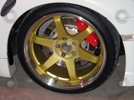 Gold rims stock photo, Custom gold rims on a white sportscar complete with performance brakes by Todd Arena
