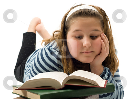 Child Studying stock photo, A young girl lying on the floor studying a textbook, isolated against a white background by Richard Nelson
