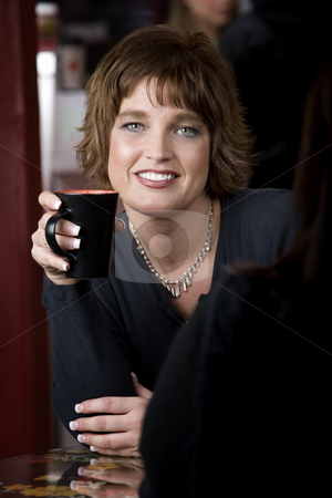 Portrait of Woman with Friend in Coffee House stock photo, Pretty adult woman with friend in a coffee house by Scott Griessel