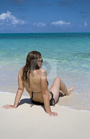 Relaxing in the tropics stock photo, Young female sitting on the water's edge of a beautiful tropical beach. by Robert Ranson