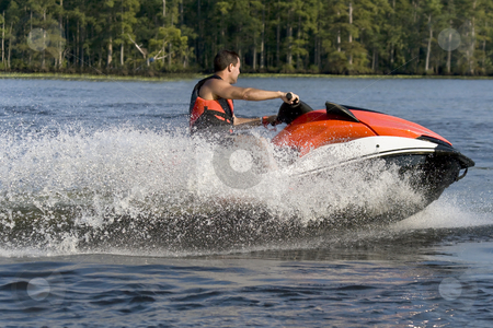 Man riding wave runner stock photo, Man riding a wave runner in a river enjoying a nice summer day. by Robert Ranson