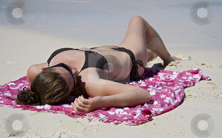Relaxing in the tropics stock photo, Young woman relaxing on a tropical beach. by Robert Ranson