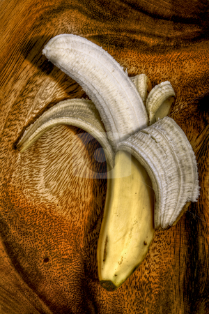 Banana stock photo, Peeled banana sitting in a wooden bowl. by Robert Ranson