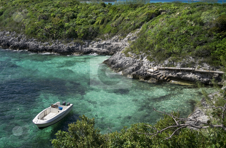 Anchored boat next to tropical island stock photo, Small boat anchored in a tropical cove next to a small island. by Robert Ranson