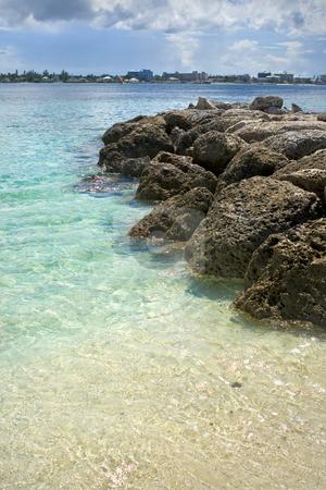 Tropical beach stock photo, Tropical beach with rocks extending into the ocean. by Robert Ranson