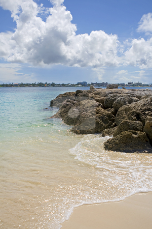 Tropical beach stock photo, Tropical beach with rocks extending into the clear blue water. by Robert Ranson