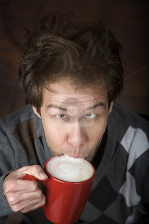 Young man drinking coffee stock photo, Young man drinking speialty coffee drink from red mug by Scott Griessel
