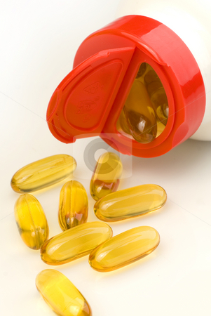 Capsules spilling out of a bottle stock photo, Vitamin capsules spilling out of a white bottle by Jonathan Hull