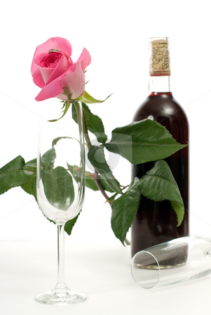 Romantic Tabletop Setting stock photo, A tabletop setting with a bottle of wine, a rose and two empty wine glasses by Richard Nelson
