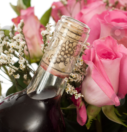 Champagne and Roses stock photo, Closeup view of a corked bottle of champagne and some pink roses by Richard Nelson