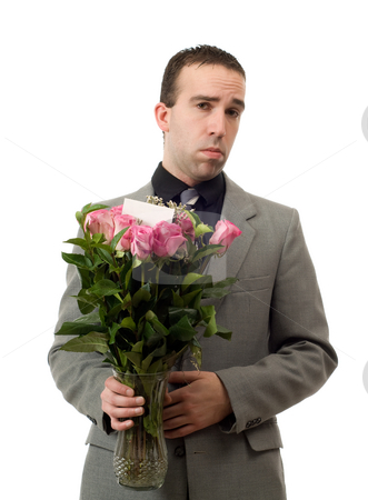 Sad Man With Flowers stock photo, A young man holding a vase of roses with a sad expression on his face, isolated against a white background by Richard Nelson