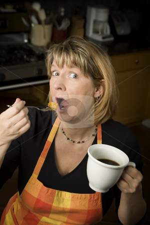 Woman eating in kitchen stock photo, Woman in kitchen with coffee eating from a fork by Scott Griessel
