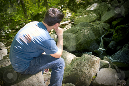 Thinking by the Waterfall stock photo, A young man in deep thought while sitting on some rocks near a beautiful waterfall. by Todd Arena