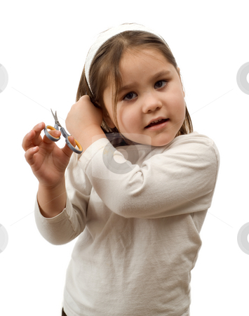 Child Cutting Their Own Hair stock photo, A young girl about to cut her own hair with a pair of scissors, isolated against a white background by Richard Nelson