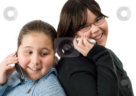 Girl Talk stock photo, Two girls talking on cell phones, isolated against a white background by Richard Nelson