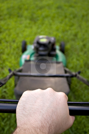 Pushing the Lawn Mower stock photo, The interesting point of view from a man pushing a lawn mower.  Shallow depth of field. by Todd Arena