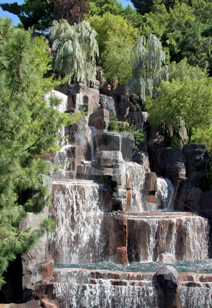 Waterfall stock photo, A lush waterfall in the middle of green pine trees by Kevin Tietz