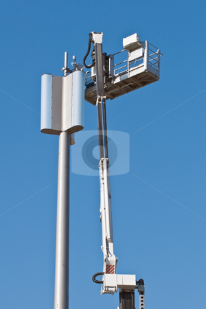 GSM antenna stock photo, Installation of a GSM antenna with a worker on platform by Massimiliano Leban