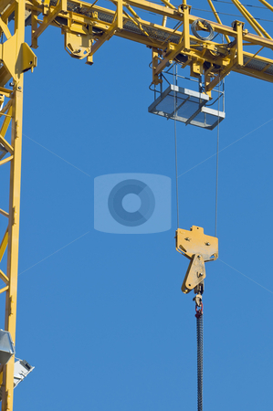Crane stock photo, Detail of yellow crane with hook against a blue sky by Massimiliano Leban