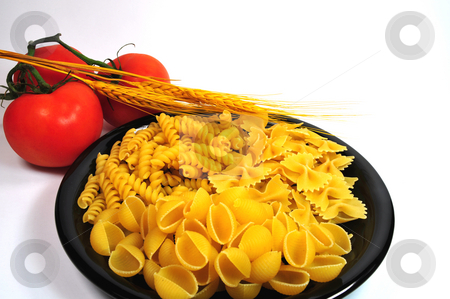 Dried Pasta stock photo, Assorted dried pasta on a black plate with tomatoes and wheat stalks by Lynn Bendickson