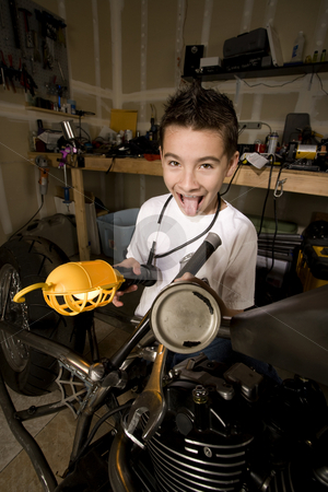 Silly Boy Mechanic stock photo, Silly Young Boy Mechanic Working on a Chopper Motorcycle by Scott Griessel