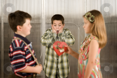 Valentine Gift stock photo, Little girl giving a candy heart to boy causes concern by Scott Griessel