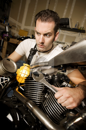 Overwhelmed Mechanic stock photo, Overwhelmed man in residential garage working on chopper-style motorcycle by Scott Griessel