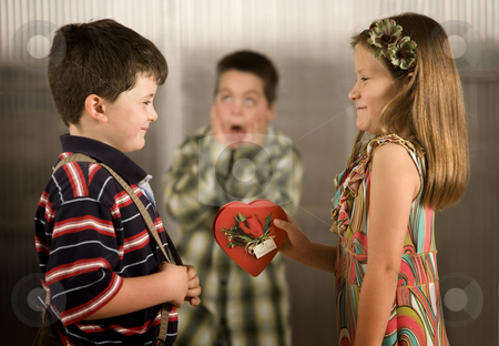Valentine Reaction stock photo, Little girl giving boy a Valentine gets reaction from third child by Scott Griessel