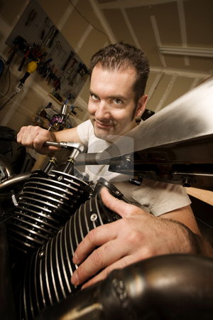 Man in garage working on motocycle stock photo, Man in residential garage working on chopper-style motorcycle by Scott Griessel
