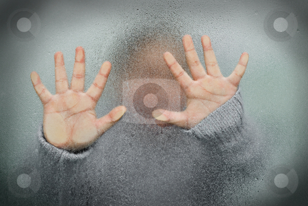 Trapped Child stock photo, A young girl trapped behind some frosted glass with her hands on it by Richard Nelson