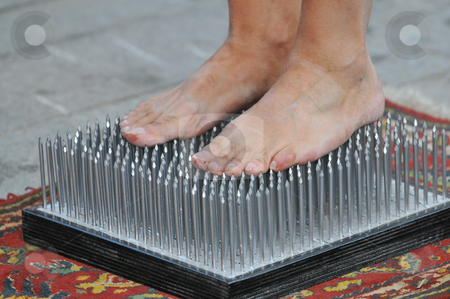 Bed of nails stock photo, Fakir foots standing on a nails bed by Massimiliano Leban