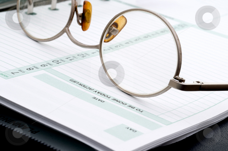 Eye glasses on a day planner stock photo, Eye glasses on a business day planner by Vince Clements
