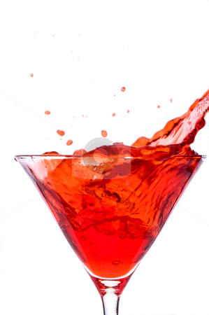 A cube od ice spalshing into a red martini alcoholic beverage stock photo, A cube od ice spalshing into a red martini alcoholic beverage by Vince Clements