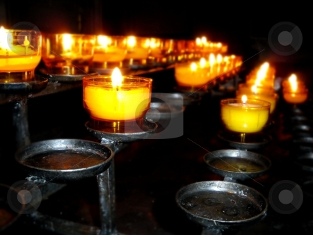 Church Candles stock photo, Burning candles in a church for worship. by Henrik Lehnerer