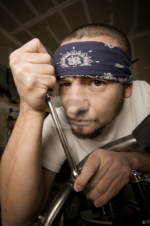 Hispanic Mechanic stock photo, Hispanic mechanic working on a chopper style motorcycle by Scott Griessel