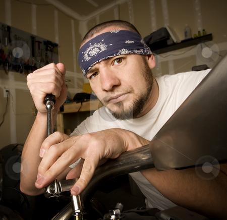 Hispanic Mechanic stock photo, Hispanic mechanic working on a chopper style motorcycle by Scott Griessel