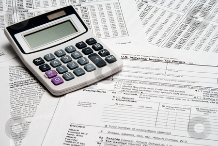 Tax Calculator stock photo, A calculator sitting on top of tax forms. by Robert Byron