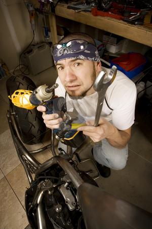 Hipsanic Mechanic stock photo, Hispanic mechanic working on a chopper style motorcycle by Scott Griessel