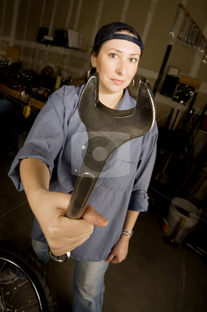 Hispanic woman in a agarage stock photo, Hispanic woman in a garage with wrench by Scott Griessel