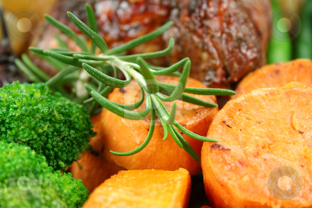 Rosemary And Baked Vegetables stock photo, A sprig of rosemary with baked carrots, sweet potato and broccoli. by Brett Mulcahy