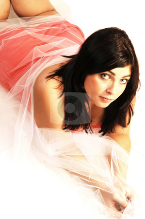 Woman lying on the floor.  stock photo, An black haired young woman lying on the floor with in a pink dress and white twill over her body. by Horst Petzold