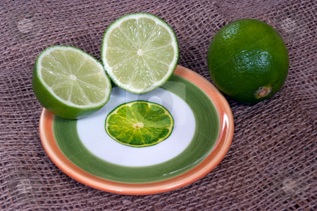 Fresh lime stock photo, A halved lime and whole lime on a decorative plate with lime illustration by Paul Phillips
