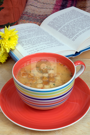Comfort stock photo, An oversized cup with hot soup on a tray with book and flower by Paul Phillips