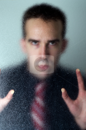 Trapped Businessman stock photo, A spooky scene of a businessman trapped behind some frosted glass by Richard Nelson