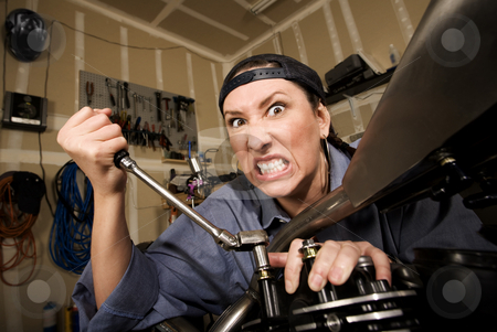 Funny Female Hispanic Mechanic stock photo, Funny female Hispanic mechanic  working on a chopper style motorcycle by Scott Griessel