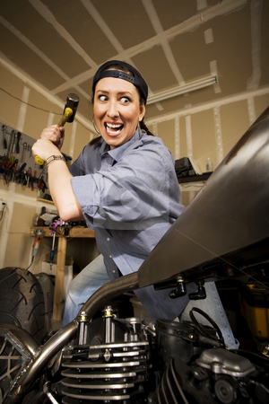 Woman taking a sledghammer to a motorcycle stock photo, Hispanic woman swinging a sledgehammer at a motorcycle by Scott Griessel