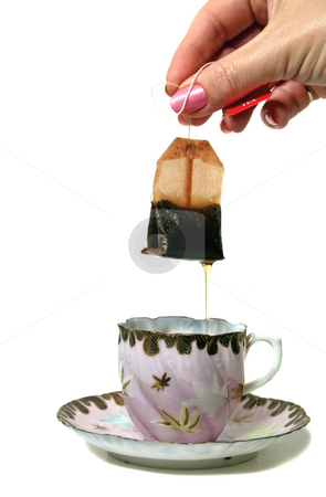 Dripping Tea bag stock photo, Dripping tea bag held above an antique teacup and saucer. by Brett Mulcahy