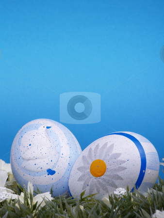 Two easter eggs stock photo, Handpainted easter eggs, artificial grass and blossoms, shades of blue background by Torsten Lorenz