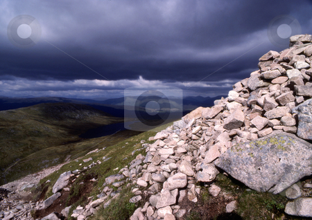 Storm clouds gathering stock photo, A stormy sky and rock face high on a mountain range in Scotland by Paul Phillips