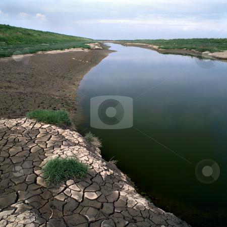 Dry river stock photo, An almost dry river bed with ctacked earth by the sides by Paul Phillips